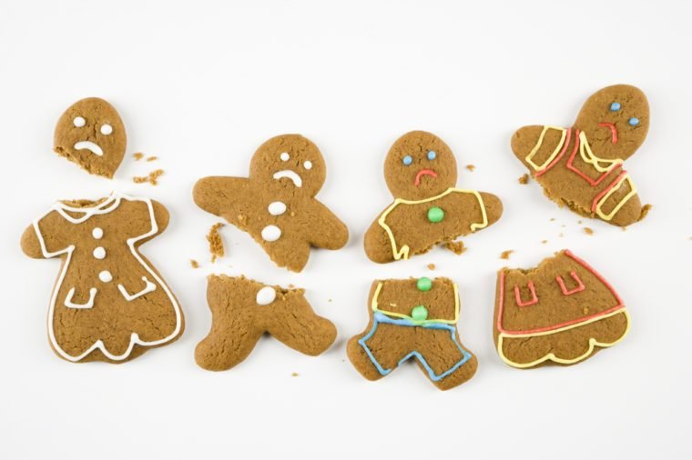 Four frowning male and female gingerbread cookies broken into pieces.