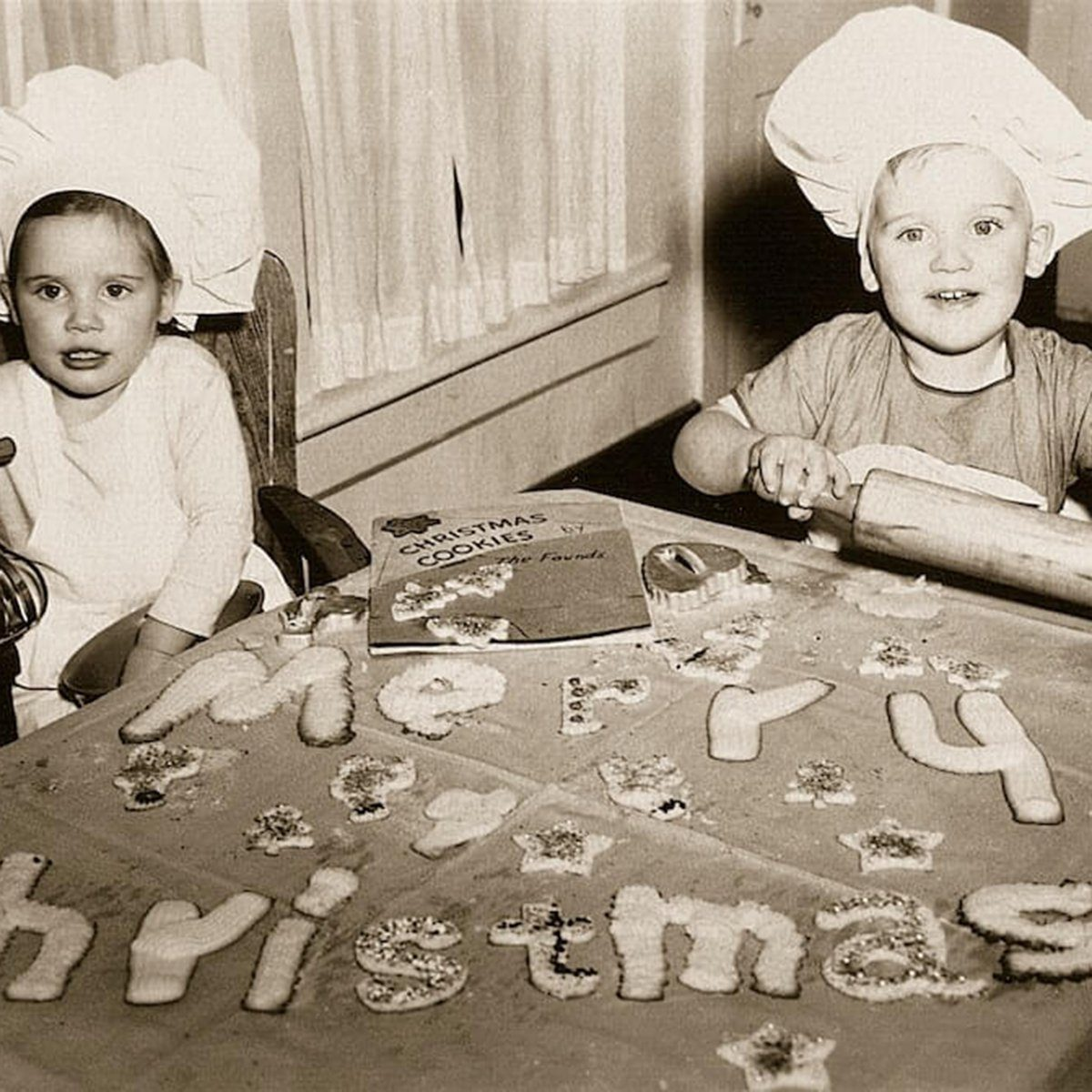 "Black and white photo of two kids spelling out ""Merry Christmas"" with cookies"