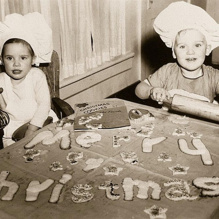 """Black and white photo of two kids spelling out """"Merry Christmas"""" with cookies"""