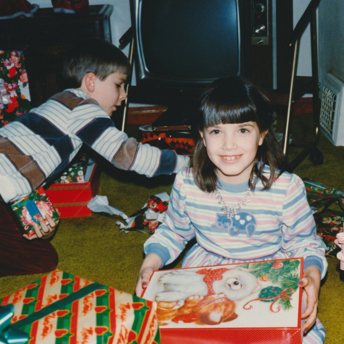 Boy and a girl opening a sea of Christmas presents