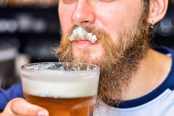 bearded man drinking beer and foam on mustache