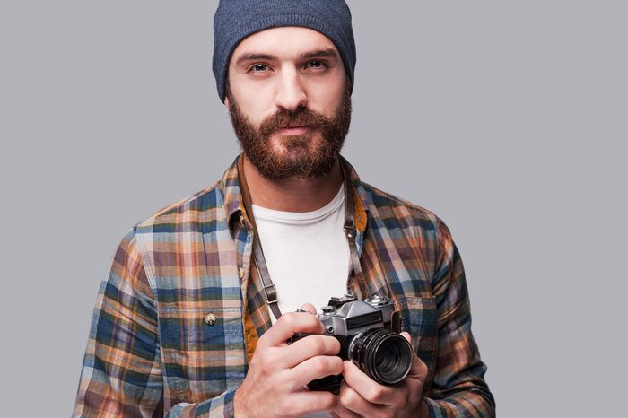 Confident photographer. Handsome young bearded man holding old-fashioned camera and looking at camera while standing against grey background