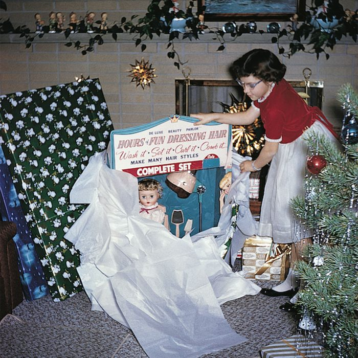 Young girl unwrapping a doll for Christmas