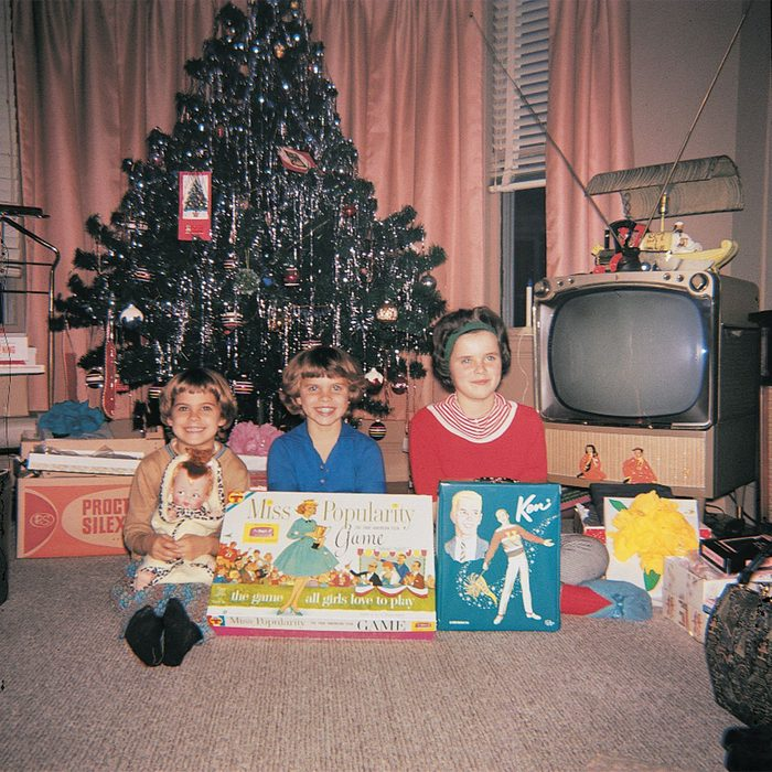 Kids posing in front of Christmas tree and opened presents