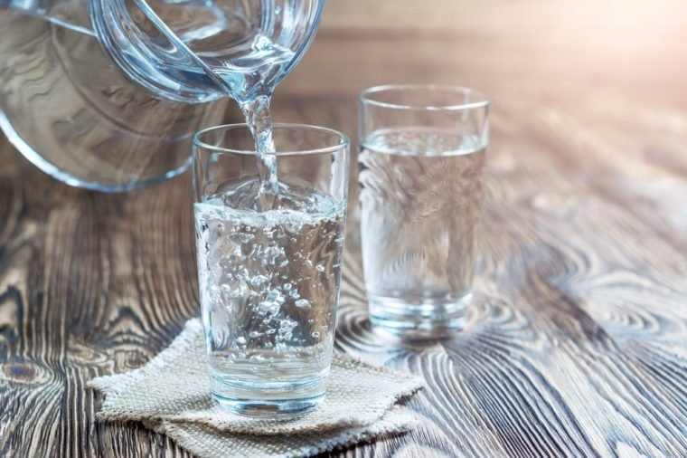 Glass of water on a wooden table. Water was poured into the beaker. Selective focus. Shallow DOF. With lighting effects. With copy space