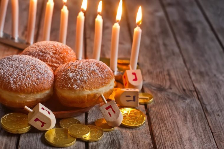 Jewish holiday hannukah symbols - menorah, doughnuts, chockolate coins and wooden dreidels. Copy space background.
