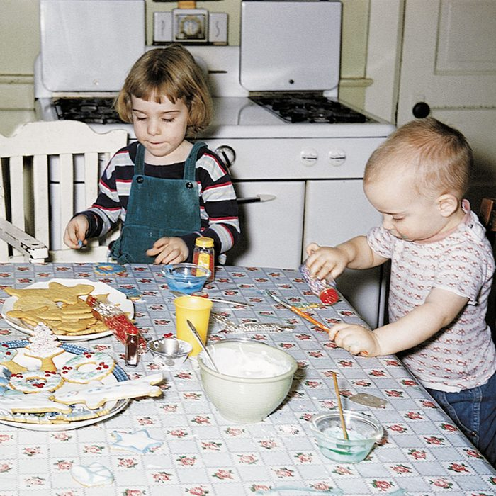 Two young kids decorating Christmas cookies