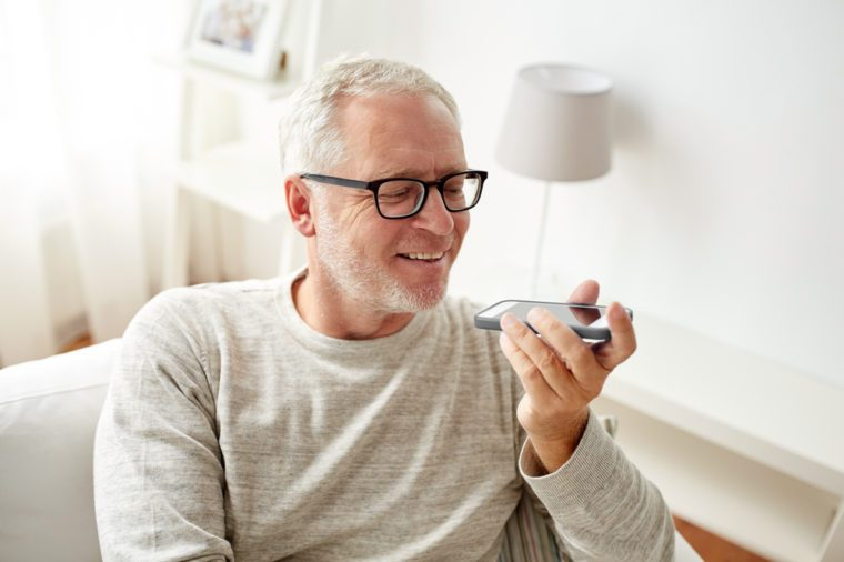 technology, people, lifestyle and communication concept - of happy senior man using voice command recorder or calling on smartphone at home