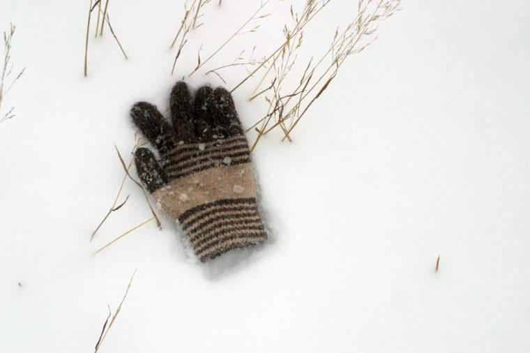 The lost children's woolen glove lies on the white snow. Winter background