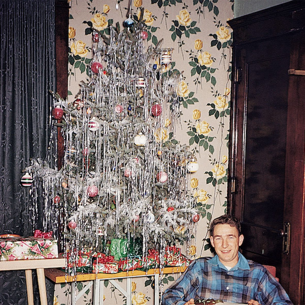 Man reclining in a chair beside a Christmas tree