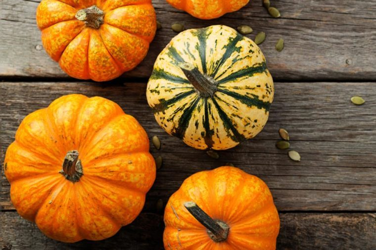 Autumn Pumpkin Thanksgiving Background - orange pumpkins over wooden table.