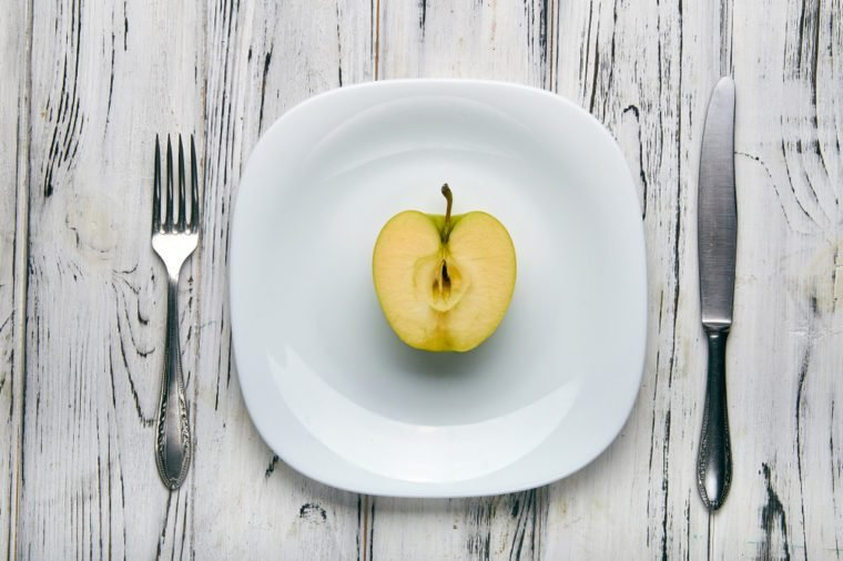 Eating for a girl, women on a strict diet. Half a green sweet and sour apple on a white plain plate. Too little food for losing weight. Anti-obesity diet by evil nutritionist.