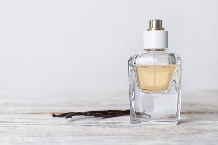 Perfume bottle and vanilla pods on wooden table against light background