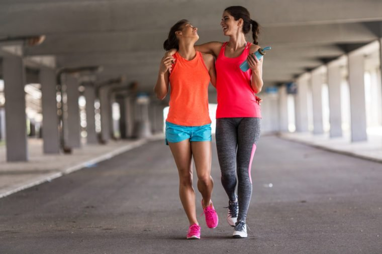 Couple of female friends jogging on the city street under the city road overpass.They relaxing after jogging and making fun.Embracing each other.