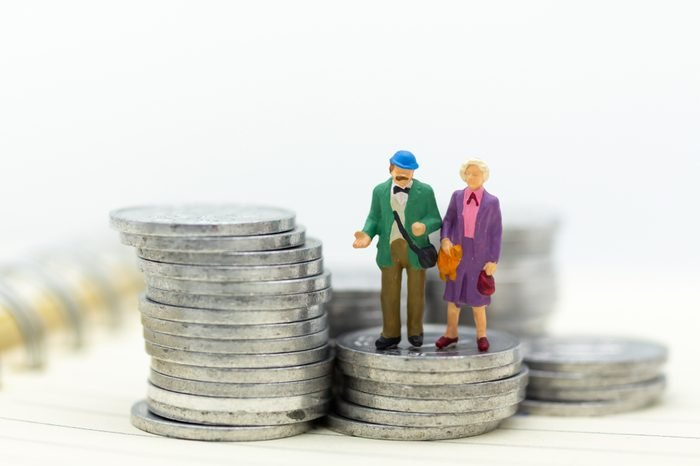 Miniature people, adult couple figure standing on top of stack coins . Image use for background retirement planning, Life insurance concept.