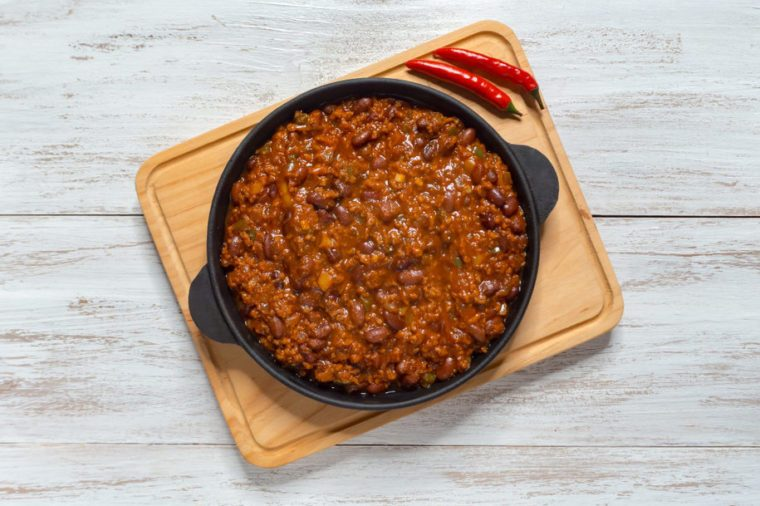 Mexican chili. Chili con carne in frying pan on white wooden background.
