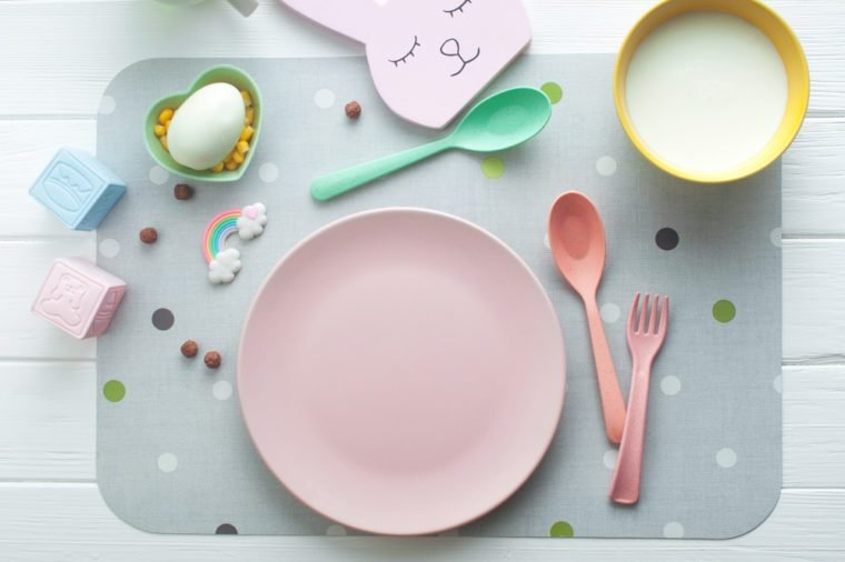 Top view of empty pink plate on white wooden background. Flat lay.