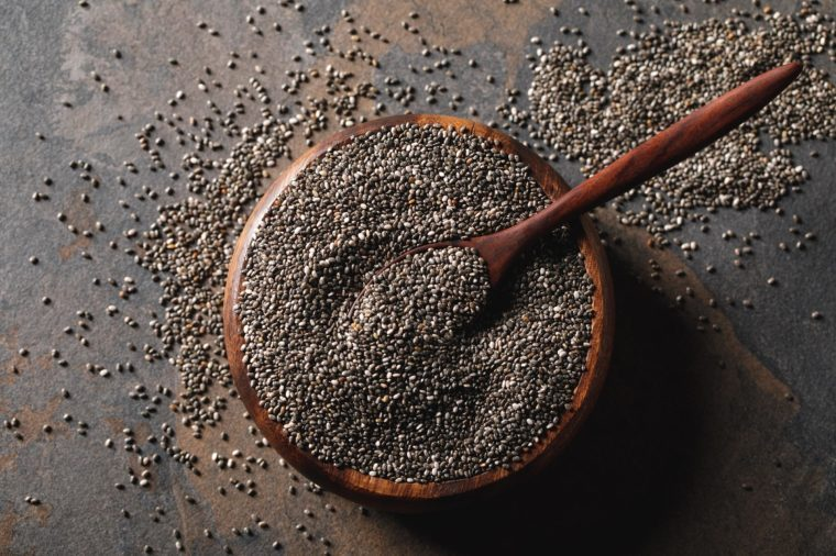 chia seeds in wooden bowl with spoon on table