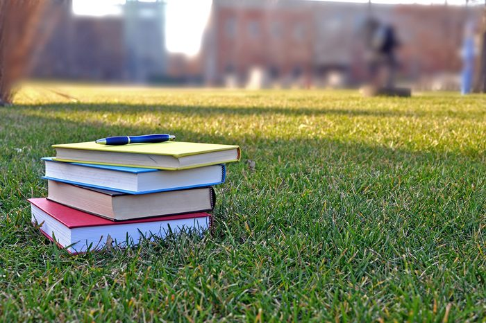 a pile of colorful books on lawn in campus
