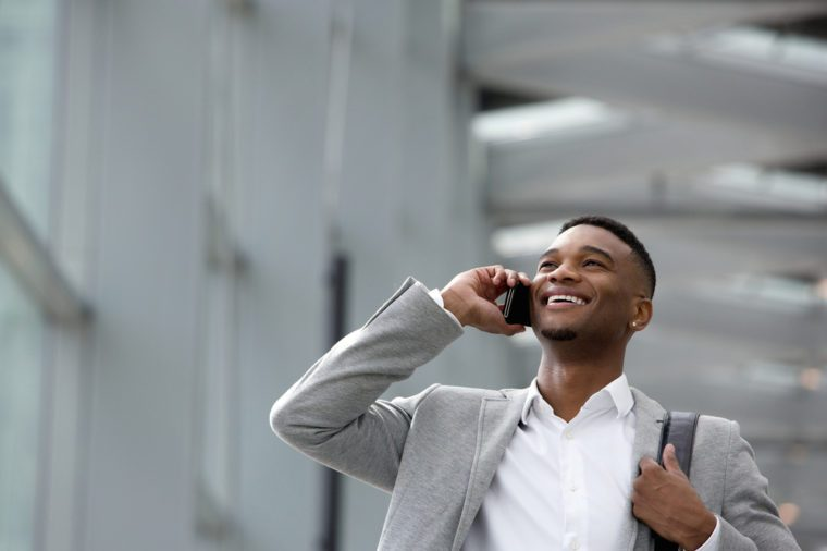 Close up portrait of a happy young man talking on mobile phone inside building