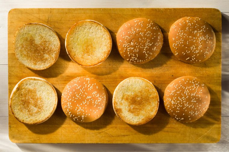 Burger buns with sesame seeds on a chopping board