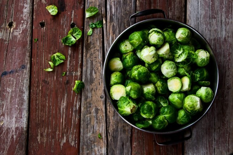 Fresh brussel sprouts over rustic wooden texture. Top view.