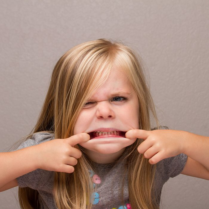 Young girl making funny faces showing her teeth; Shutterstock ID 343761566; Job (TFH, TOH, RD, BNB, CWM, CM): -