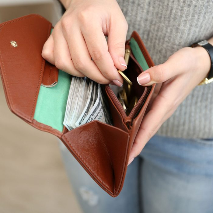 Girl with brown wallet full of money; Shutterstock ID 394142461
