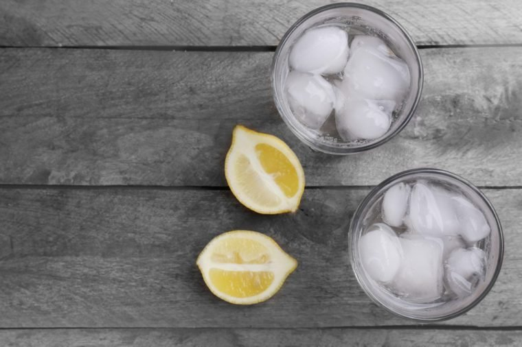 Glasses of water and sliced lemon on wooden table, top view
