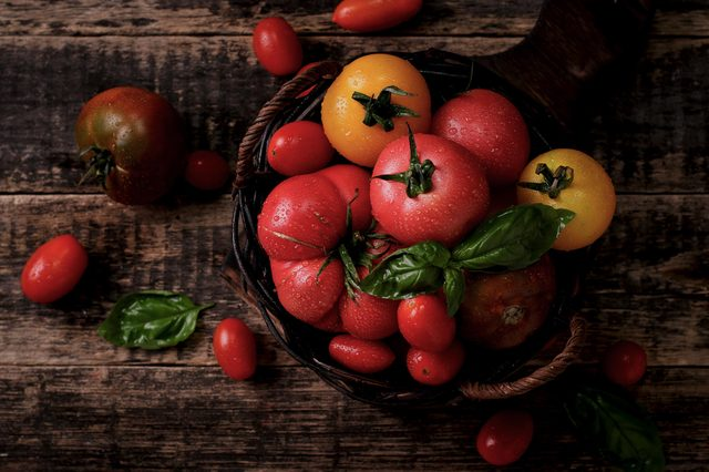 Colorful tomatoes, red , yellow , orange , green on vintage wooden background