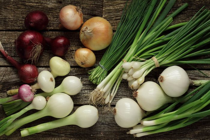Different onions and garlic on wooden background