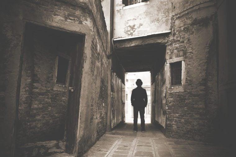 Man walking in a old mystic dark alley