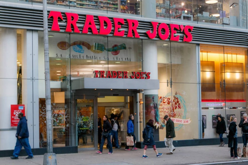 People walk by a Trader Joe's grocery store