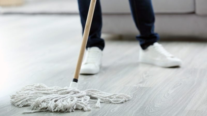 Young man with mop cleaning floor at home, closeup
