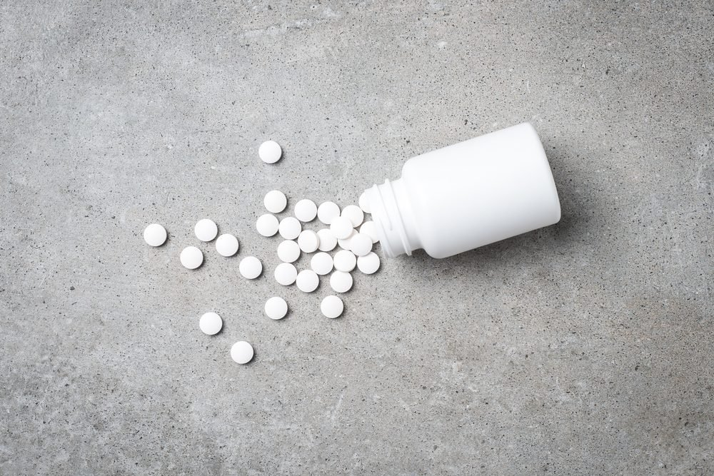 Pill bottle on gray stone background