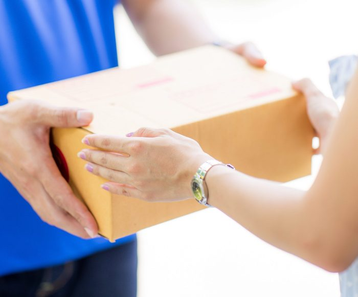 Asian woman receiving a package at home from a delivery guy; Shutterstock ID 613872155; Job (TFH, TOH, RD, BNB, CWM, CM): -