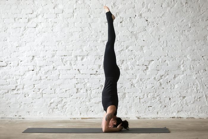 Young yogi attractive woman practicing yoga concept, standing in salamba sirsasana exercise, headstand pose, working out, wearing sportswear, black tank top and pants, full length, loft background