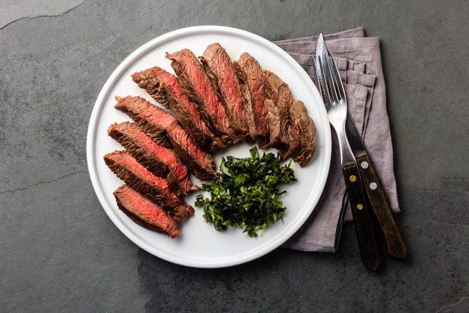 Medium rare sliced beef served on white with herb sauce and vintage cutlery set. Sliced medium rare roast beef on slate gray background