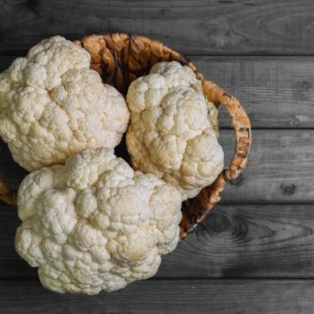 Fresh white heads cleaned cauliflower in a wicker basket for cauliflower. Rustic gray wooden background. Top view, blank space.