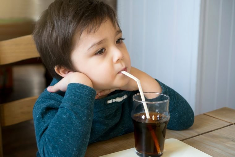 Cute toddler drinking cold drink, Little boy drink soda or soft drink through straw sitting on the chair in English pub, Child waiting for food with bored face