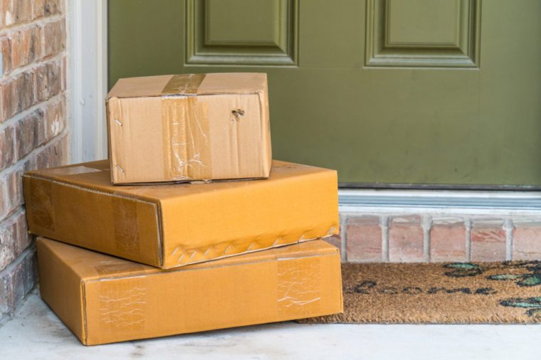 Package delivery on doorstep. Boxes and postal delivery on modern brick home doorstep on front with 3 cardboard boxes