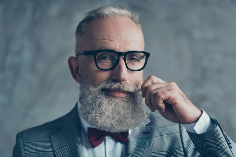 Close up portrait of grinning old-fashioned trendy elegant wealthy professional flirty trendsetter hipster grandpa sharp dressed with maroon bow-tie twisting white mustache isolated on grey background
