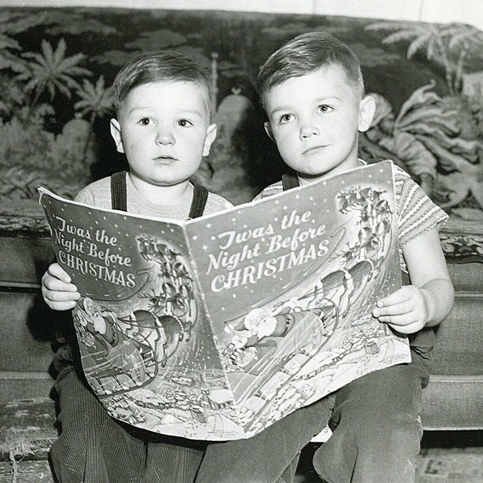 Black and white photo of two children reading a book together