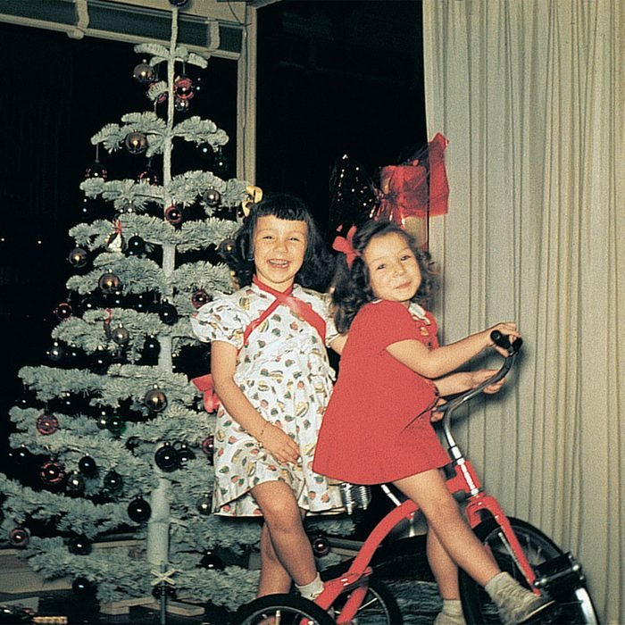 Two girls smiling and riding their new red tricycle