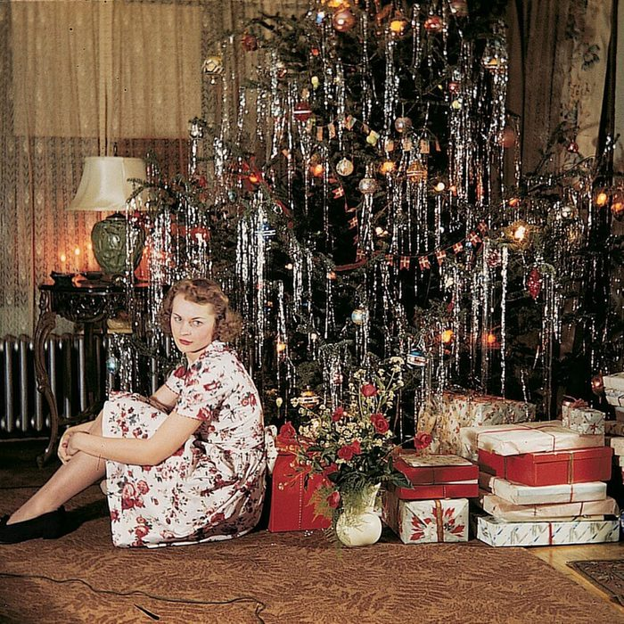 Vintage image of woman posing in front of Christmas tree