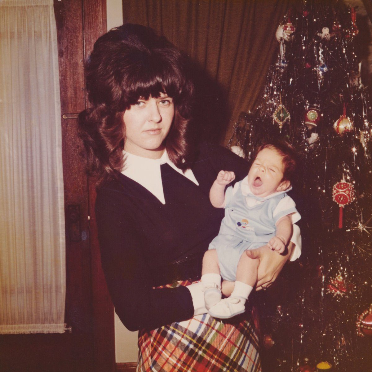 Woman holding a baby in front of a Christmas tree