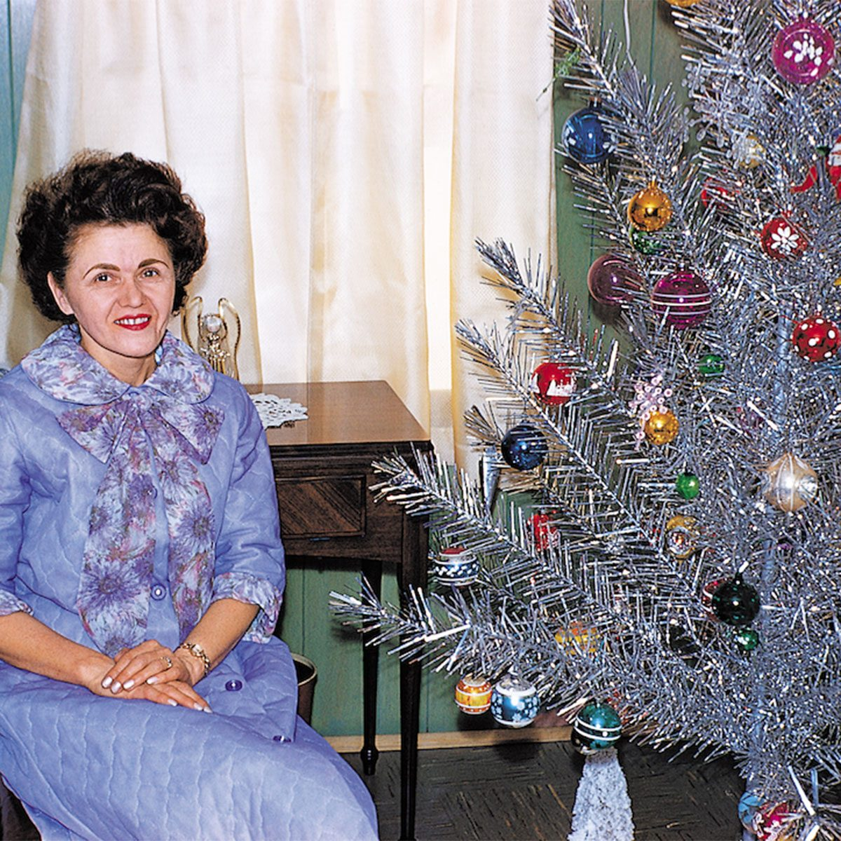 Older woman sitting beside a Christmas tree
