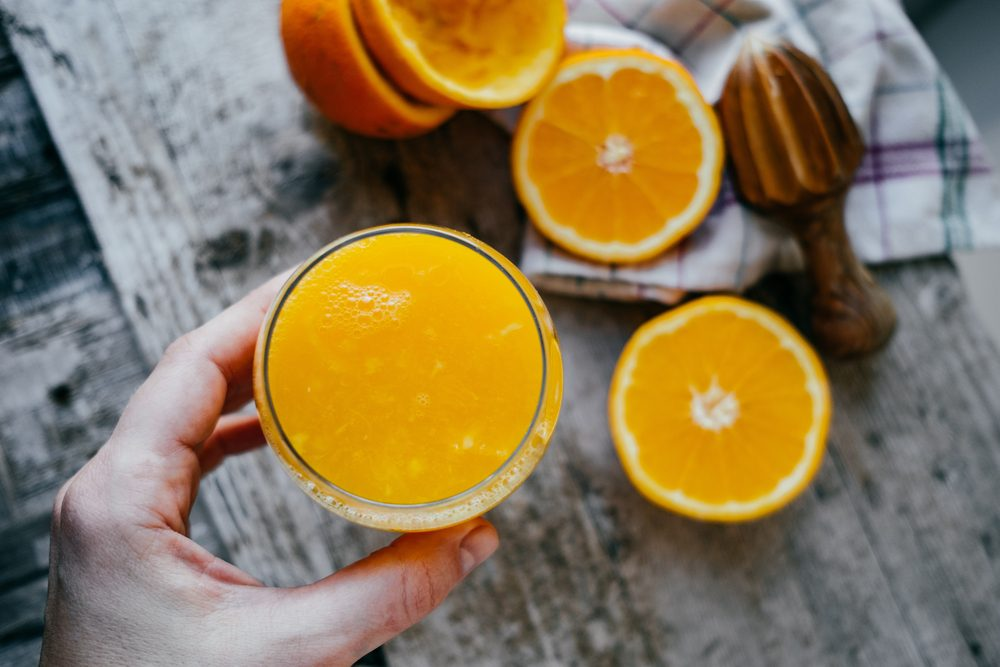 Woman Hand with juice glass and Oranges on wooden background.