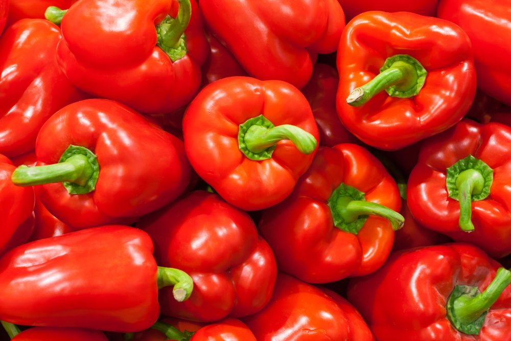 A pile of red bell peppers as background, texture