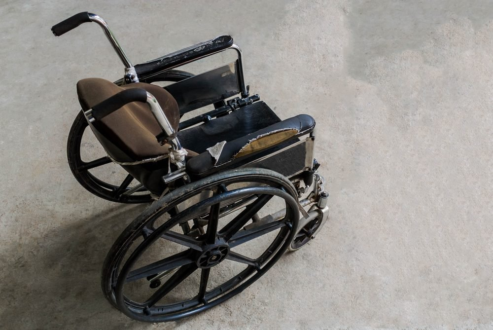 Old wheelchair ,Close-up Empty wheelchair in front of the Outpatient Department of Hospital,Close-up Empty wheelchair concept,a black and silver wheel chair on white background.